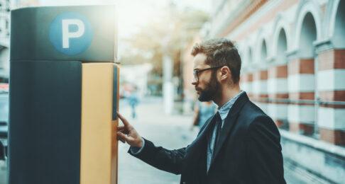 Man operates a parking ticketing machine