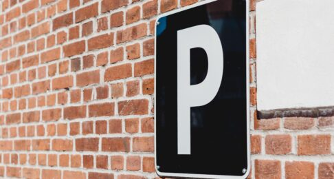 Black parking sign on a brick wall